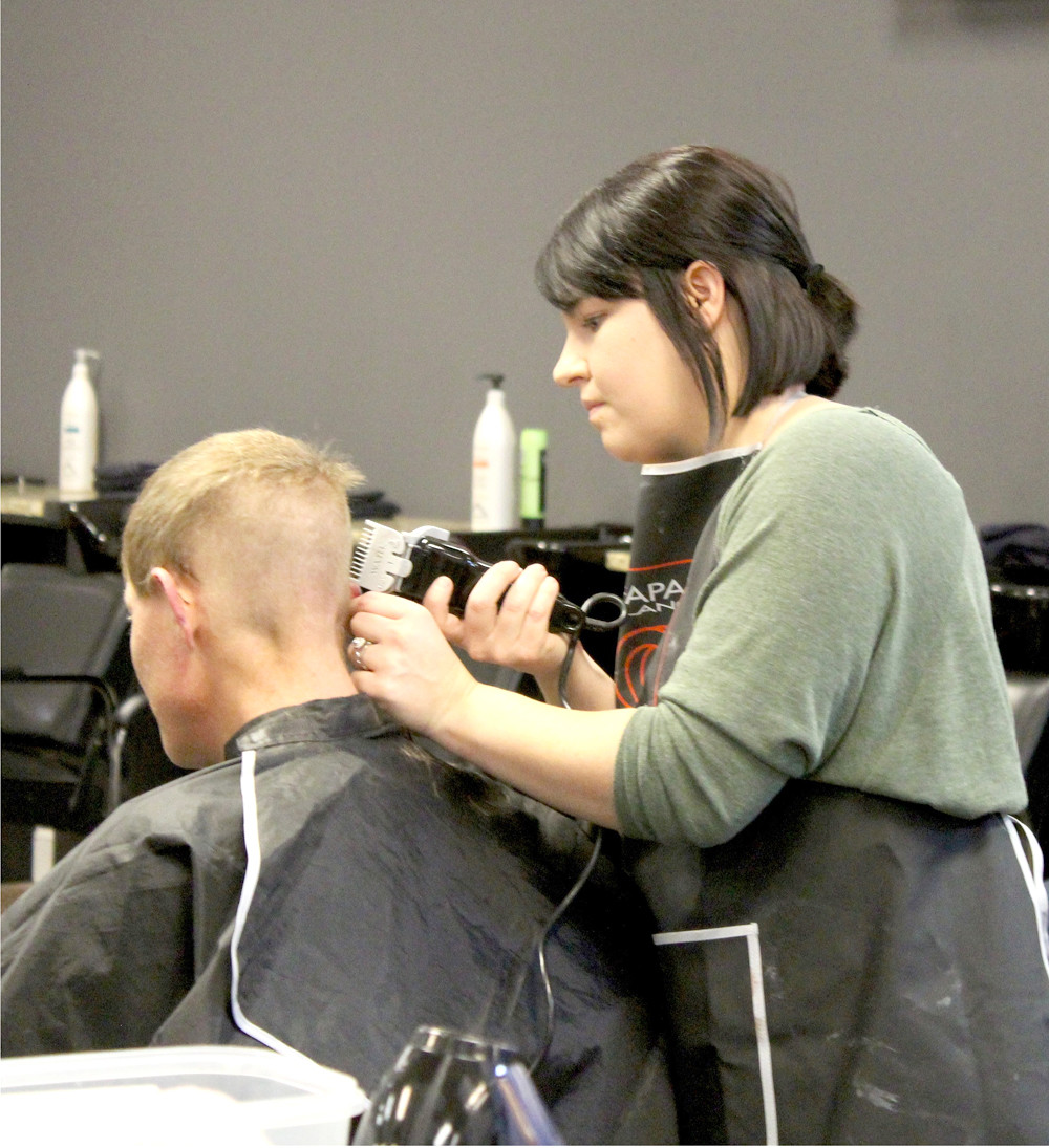 A FRANKLIN ACADEMY student carefully trims a man's hair during the cosmetology school's recent event to help the homeless and others in need before Christmas.