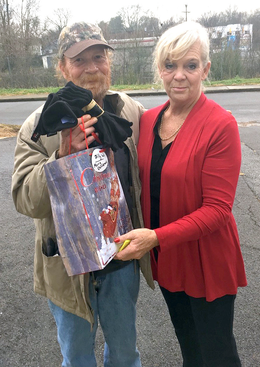TIM, A HOMELESS resident in Cleveland, displays some socks he received as a holiday gift from employees of the Lowe's Store on Paul Huff Parkways. Tim is with Diane Heil, who has helped the area's homeless for 18 years