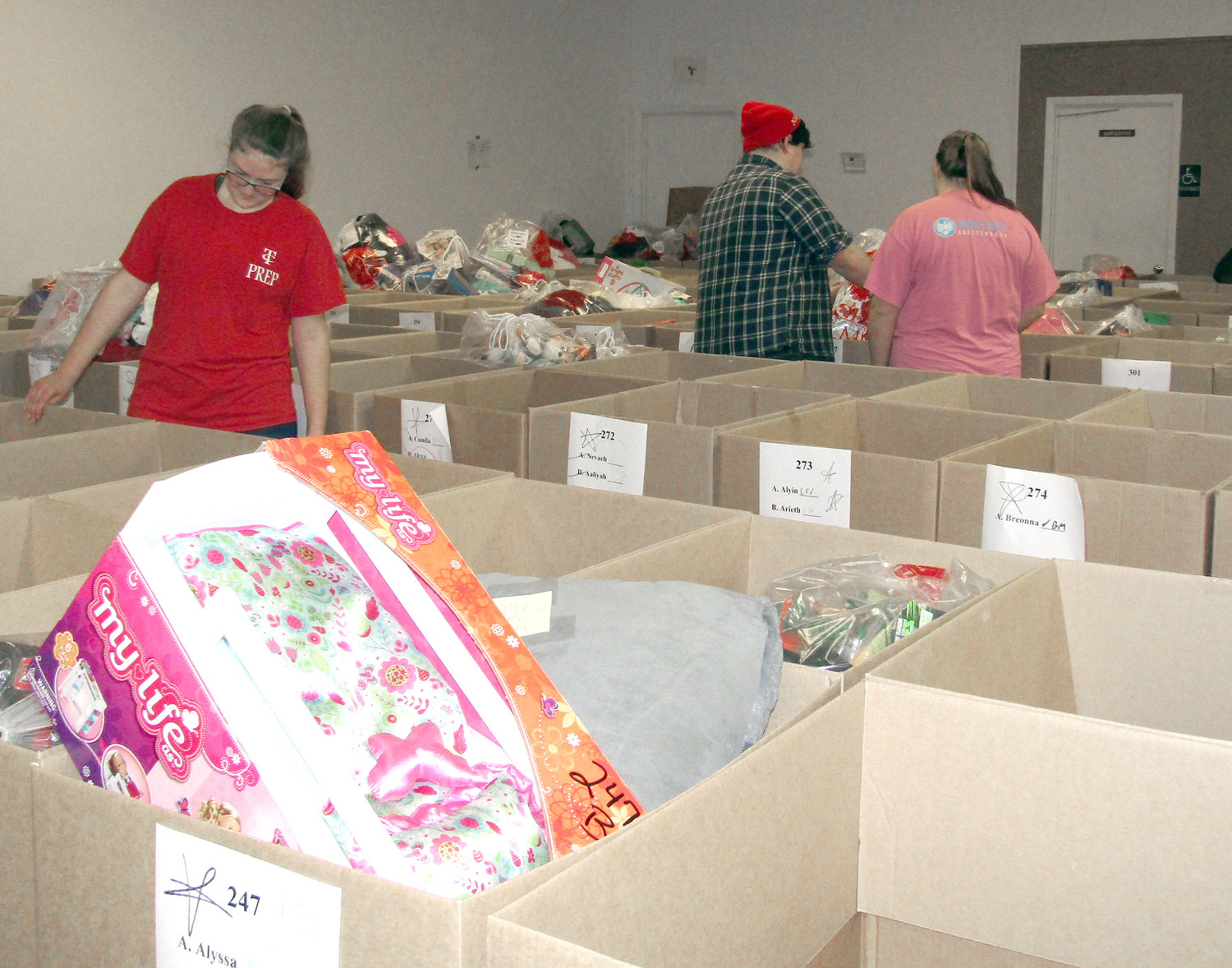 TCPS STUDENTS help organize the boxes of gifts for the Salvation Army's Angel Tree distribution.