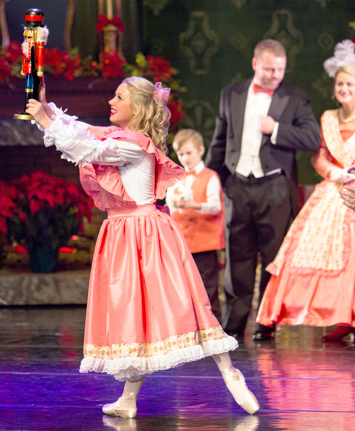 CLARA (Maddie Robinson) twirls through her parents' Christmas party, where she receives a magical Nutcracker doll from her godfather, Herr Drosselmeyer. In the background, Clara's parents (Jason and Faith Robinson) and her menacing brother, Fritz (Zachary Kline) watch the excitement closely.
