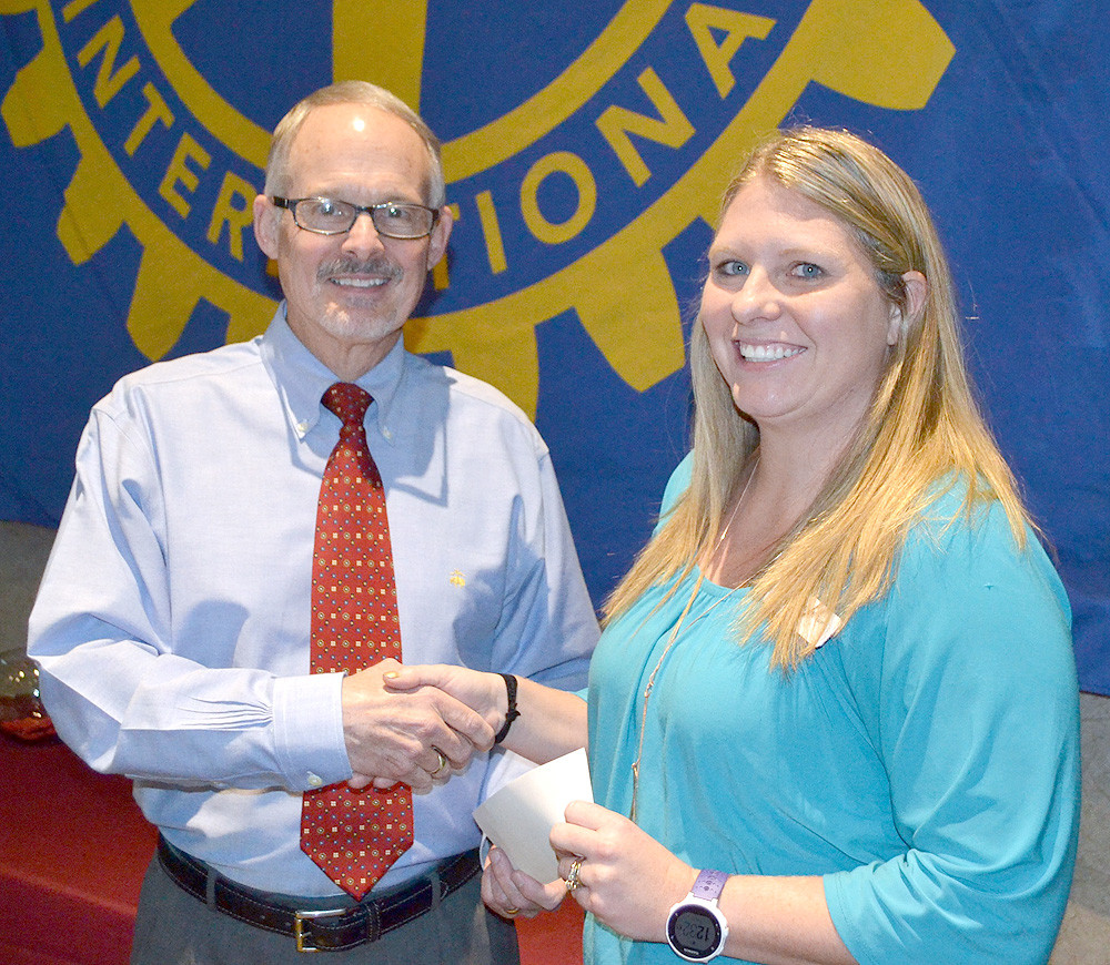DR. PAUL MCCORD, left, presents a grant from the Rotary Club of Cleveland to Elizabeth Dunn of the YCAP program.