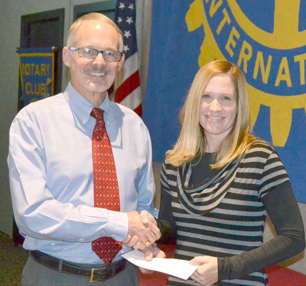 DR. PAUL MCCORD, left, presents a grant from the Rotary Club of Cleveland to Kelli Kyle of The Refuge.