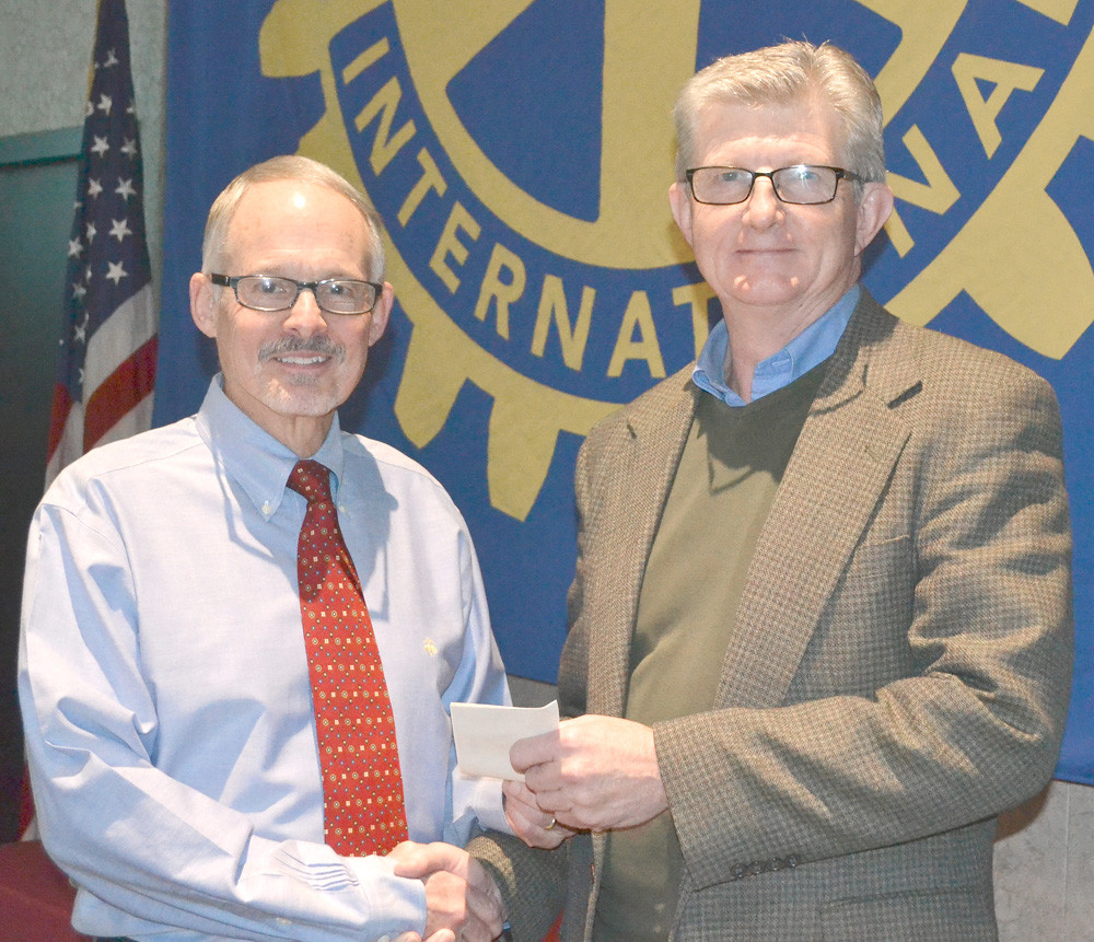 DR. PAUL MCCORD, left, presents a grant from the Rotary Club of Cleveland to Dr. Randy Howard, former executive director representing The Caring Place.