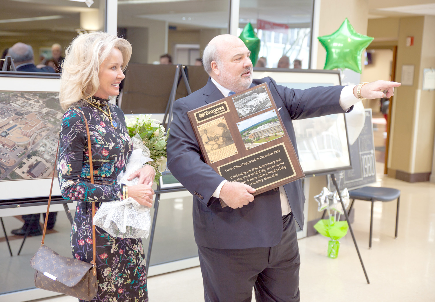 ALLAN JONES, right, points to the crowd while accepting a plaque honoring him as the first baby born at Tennova Healthcare, then known as Bradley County Memorial Hospital. Jones' wife, Janie Jones, left, was also honored as the first mother who gave birth in the new women's center, in 1984.