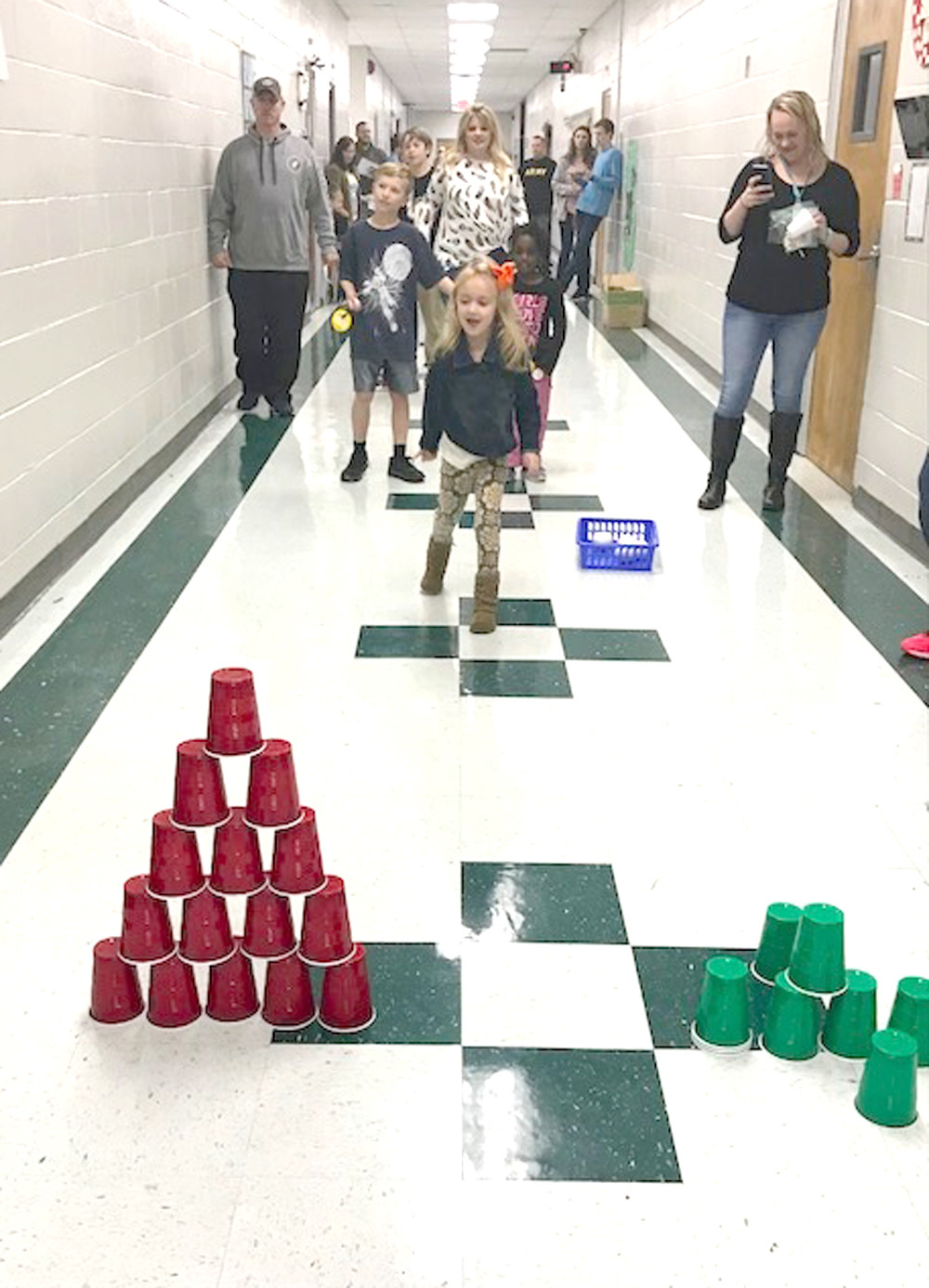 RIVER WAGNER plays a lively game in a school hallway during Old Fashioned Christmas at the Grove at Oak Grove Elementary.