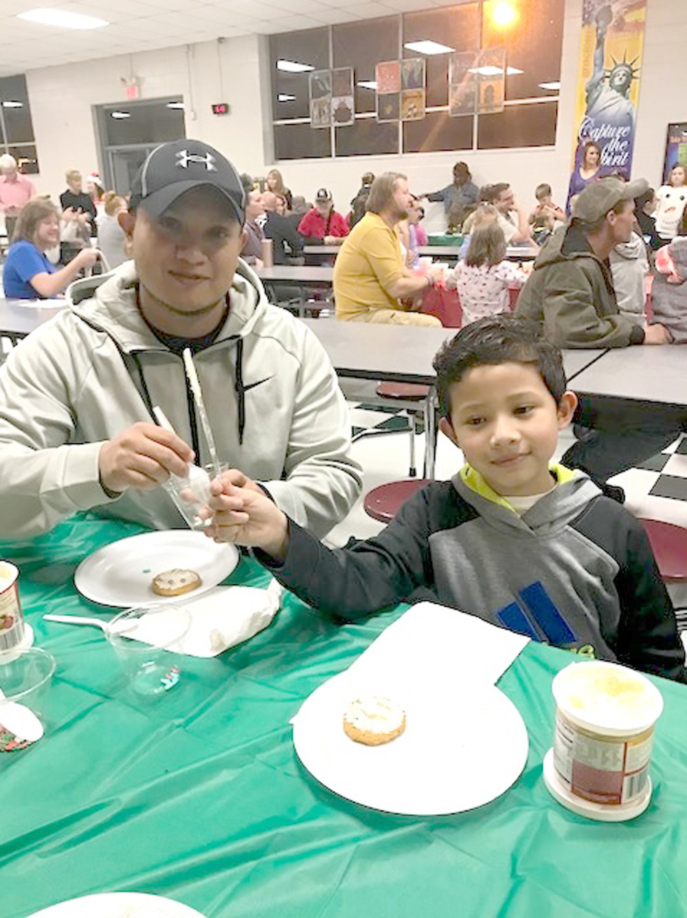 IAN GARCIA ORTIZ and his dad decorate cookies together during Old Fashioned Christmas at the Grove at Oak Grove Elementary.