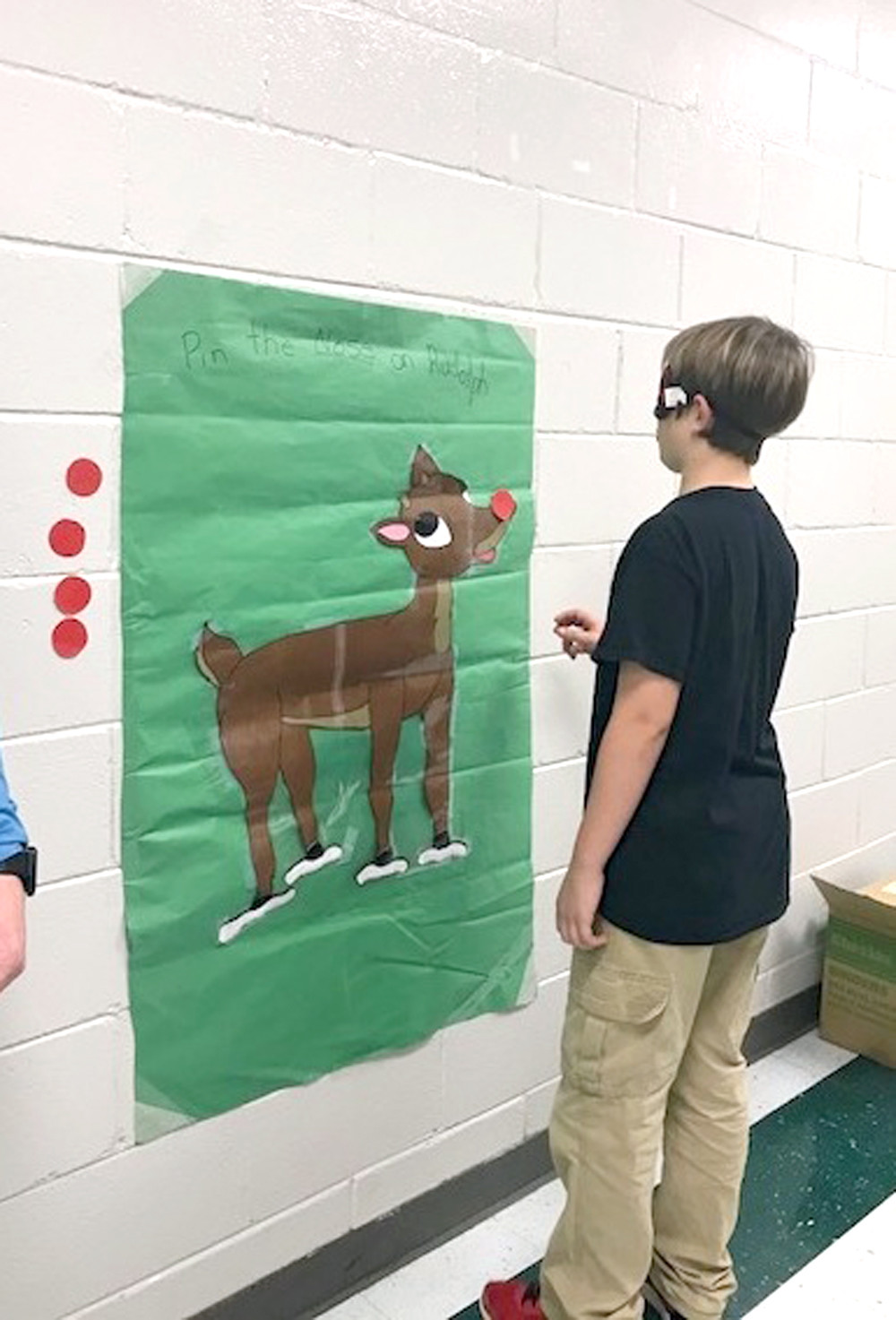 "NATE CROSS plays ""Pin the Nose on Rudolph"" during the recent Christmas event at Oak Grove Elementary School."