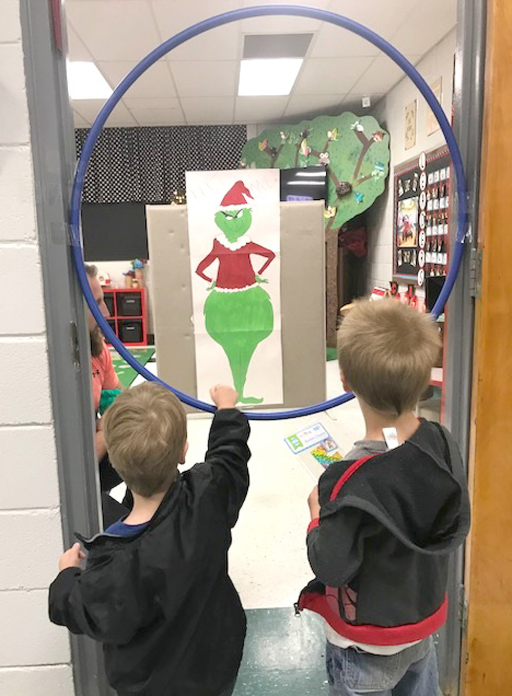 THE GRINCH seemingly taunts two students playing a game involving Dr. Seuss' infamous character, during Old Fashioned Christmas at the Grove at Oak Grove Elementary.