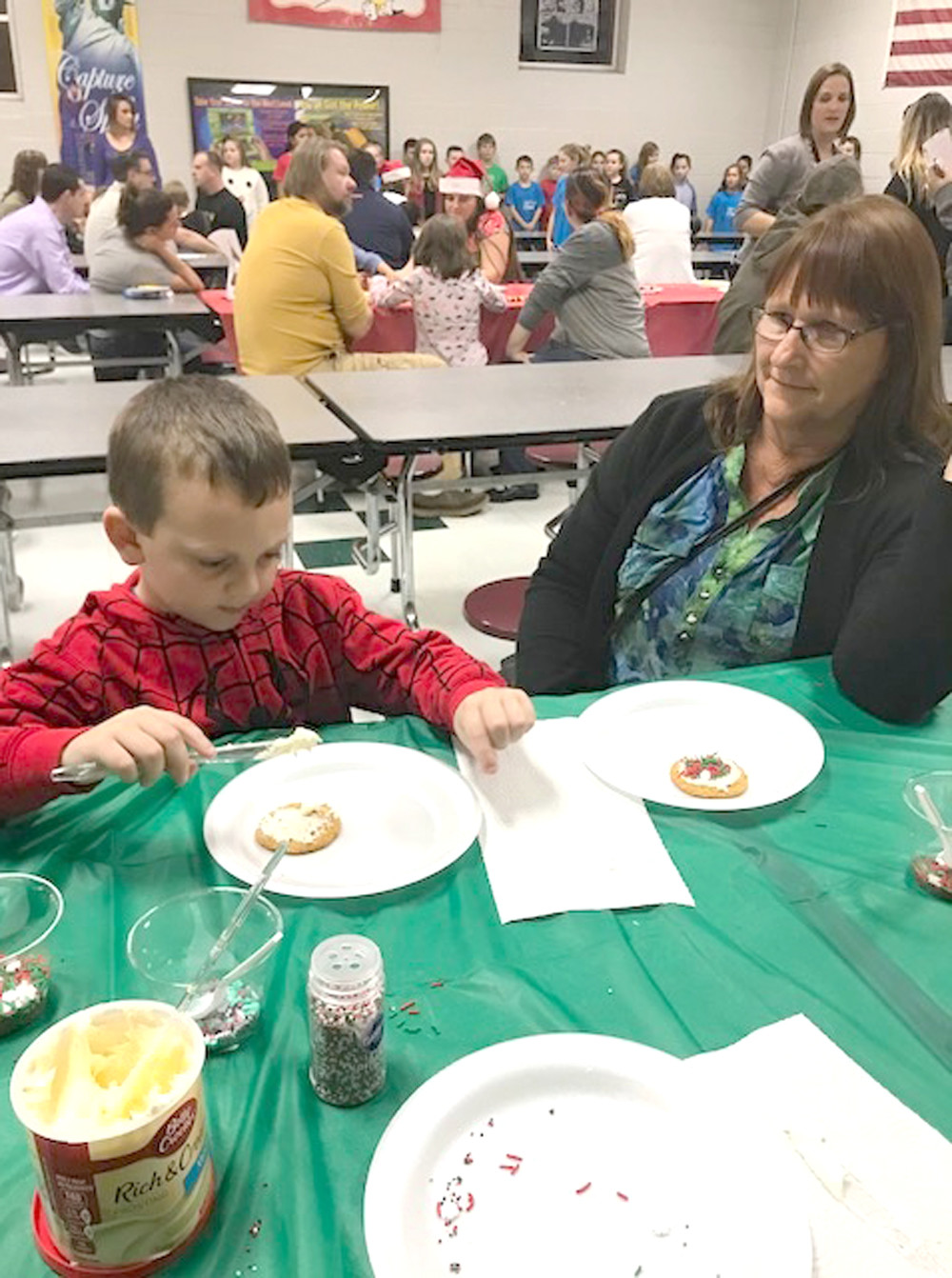 JACKERY JOHNSON and his grandmother decorate cookies during a recent family Christmas event at Oak Grove Elementary.