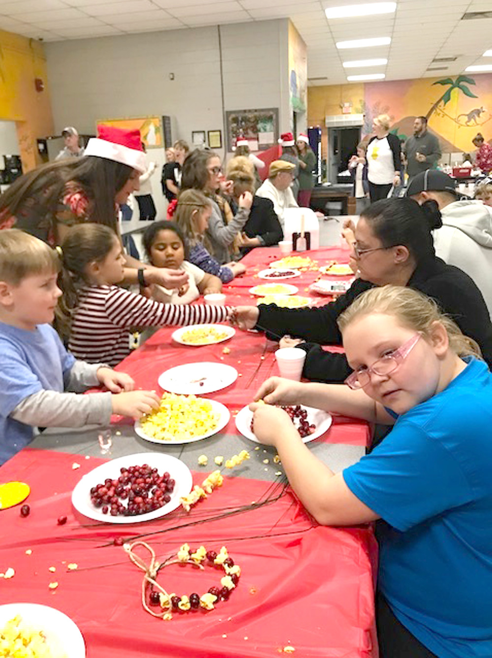 STUDENTS make decorations with popcorn and cranberries during Old Fashioned Christmas at the Grove at Oak Grove Elementary.
