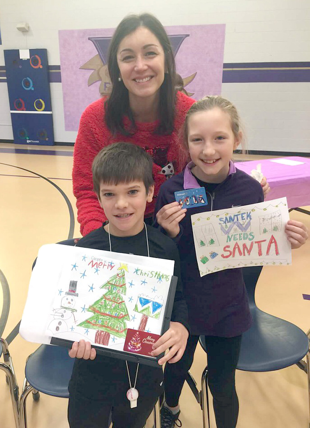 Third-grade teacher Emily Buckner proudly poses with students Cooper Weeks and Izzy Smith, and their winning card designs.
