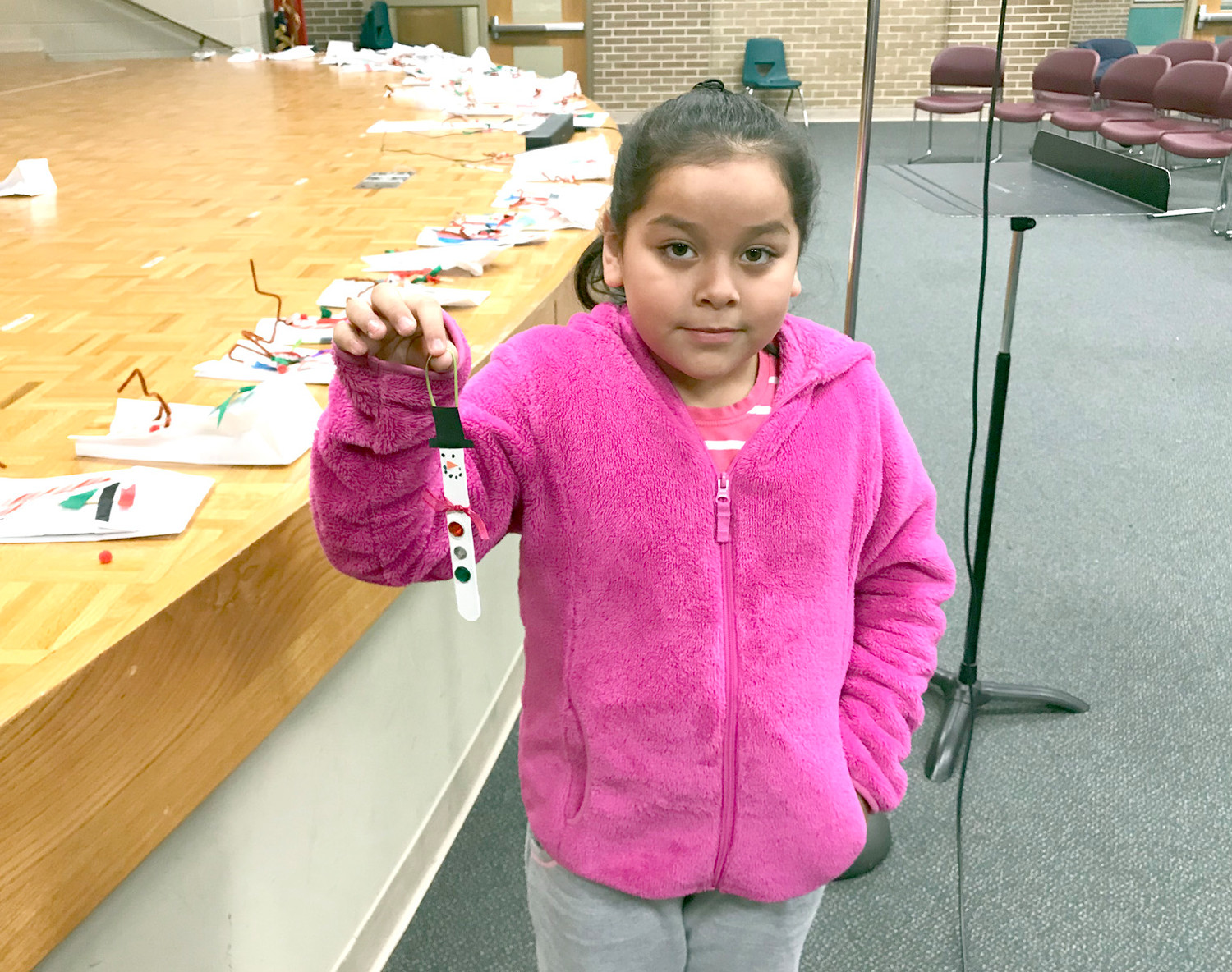 Yusli Perez shows off an ornament she made during an event at Blythe-Bower Elementary.
