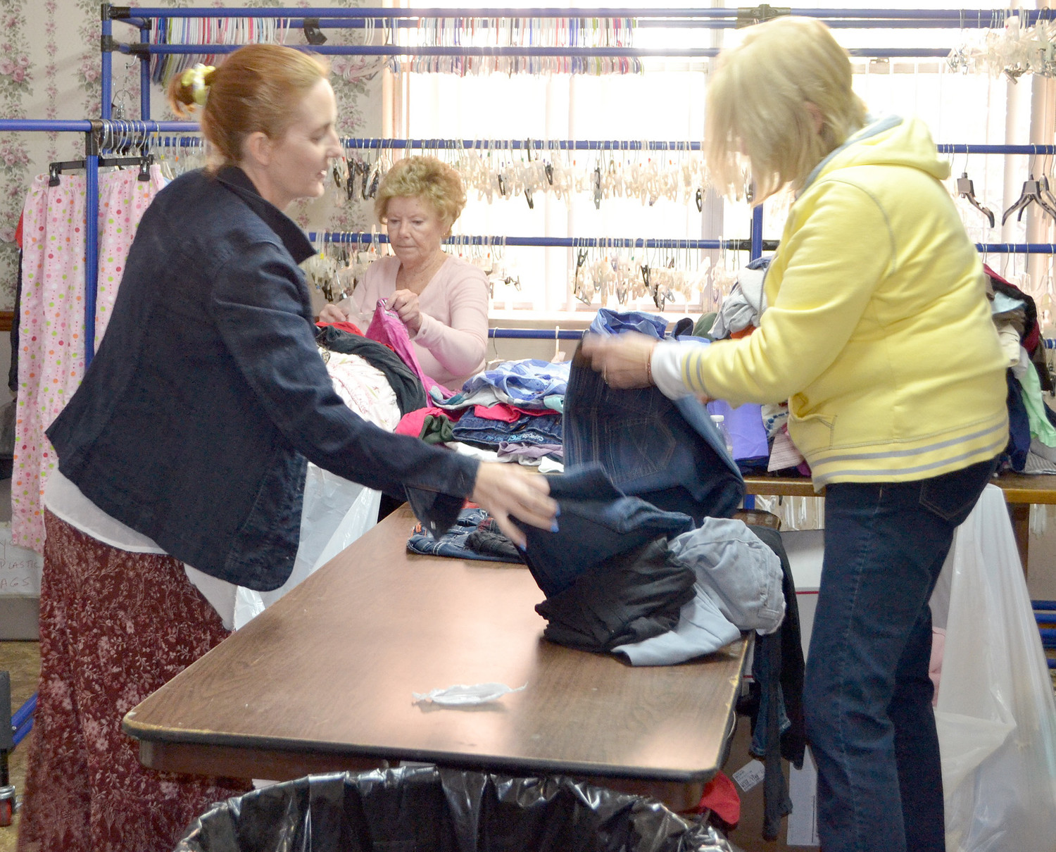 ANGIE QUIMBY, left, Margaret Firetto and Fran Lemmon, right, sort through some clothing at The Caring Place.
