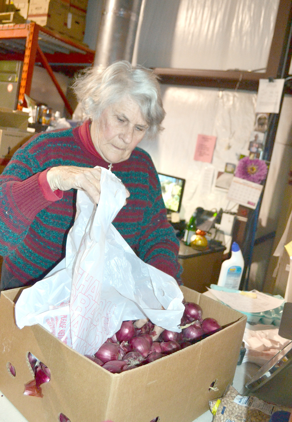 AILENE ASPRODITES prepares red onions at The Caring Place.