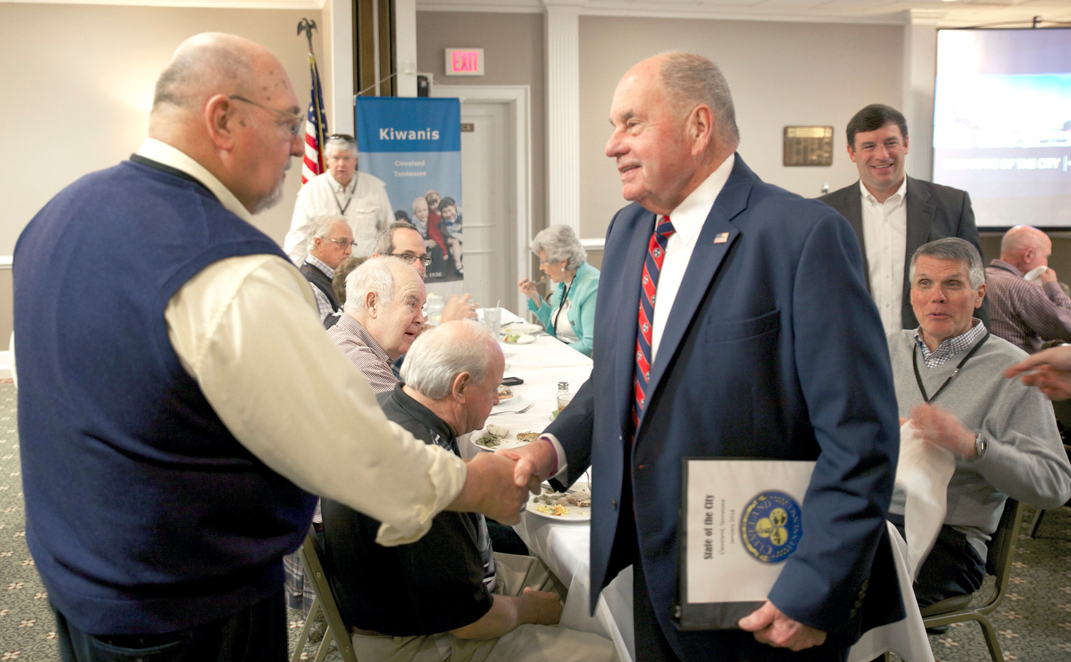 FOR YEARS, the Cleveland Kiwanis Club weekly luncheon has served as the setting for Cleveland Mayor Tom Rowland's annual State of the City address. Here, he is greeted by Doug Greene, a former Cleveland educator. In the background, at right, are Dr. Russell Dyer, director of Cleveland City Schools, who was the guest of Charlie Cogdill, a retired educator who is also a Kiwanis Club member.