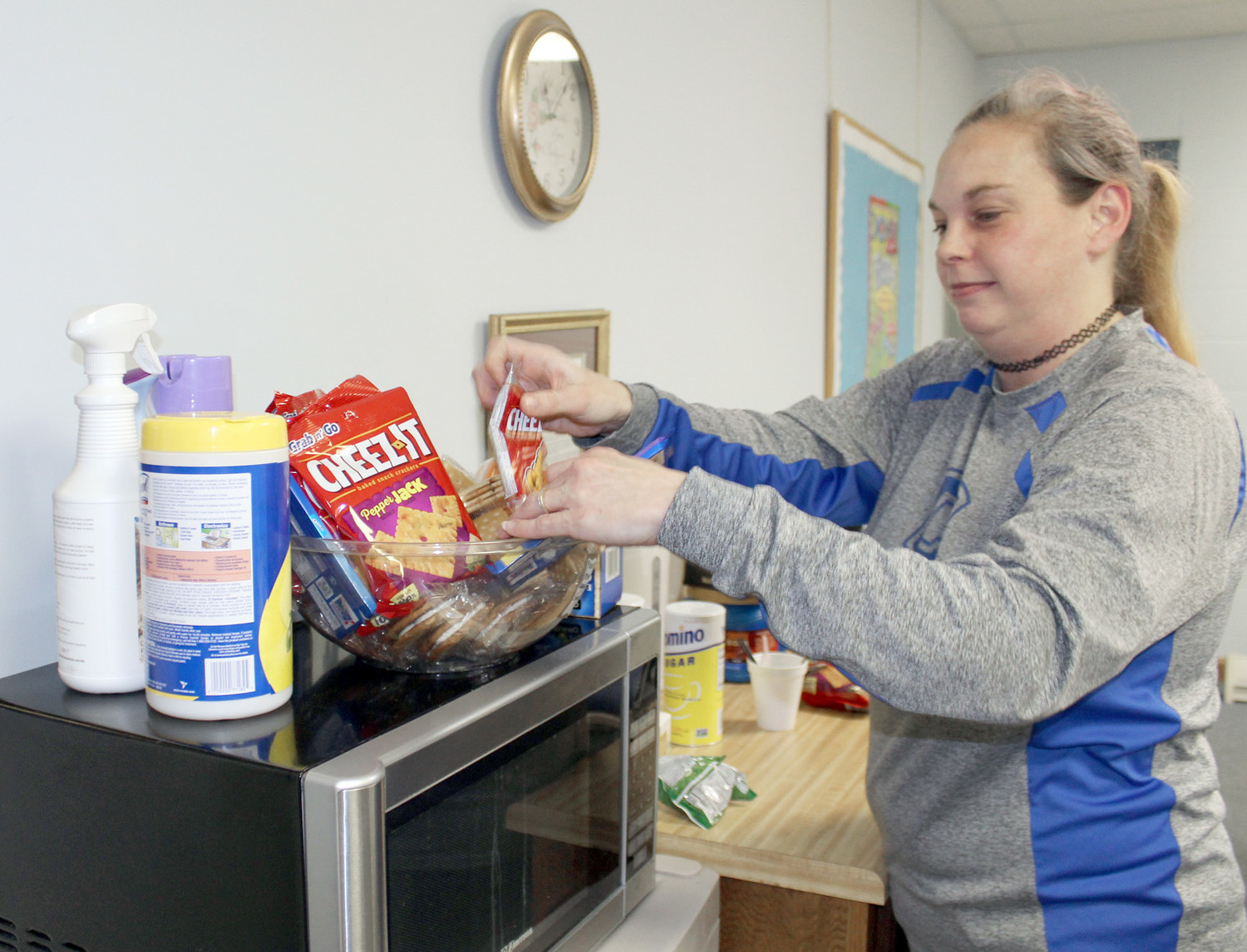 AMY MOTT, coordinator of Wesley Memorial United Methodist Church's Cold Weather Shelter, fills a snack bowl in the room used to greet those who use the church's services.