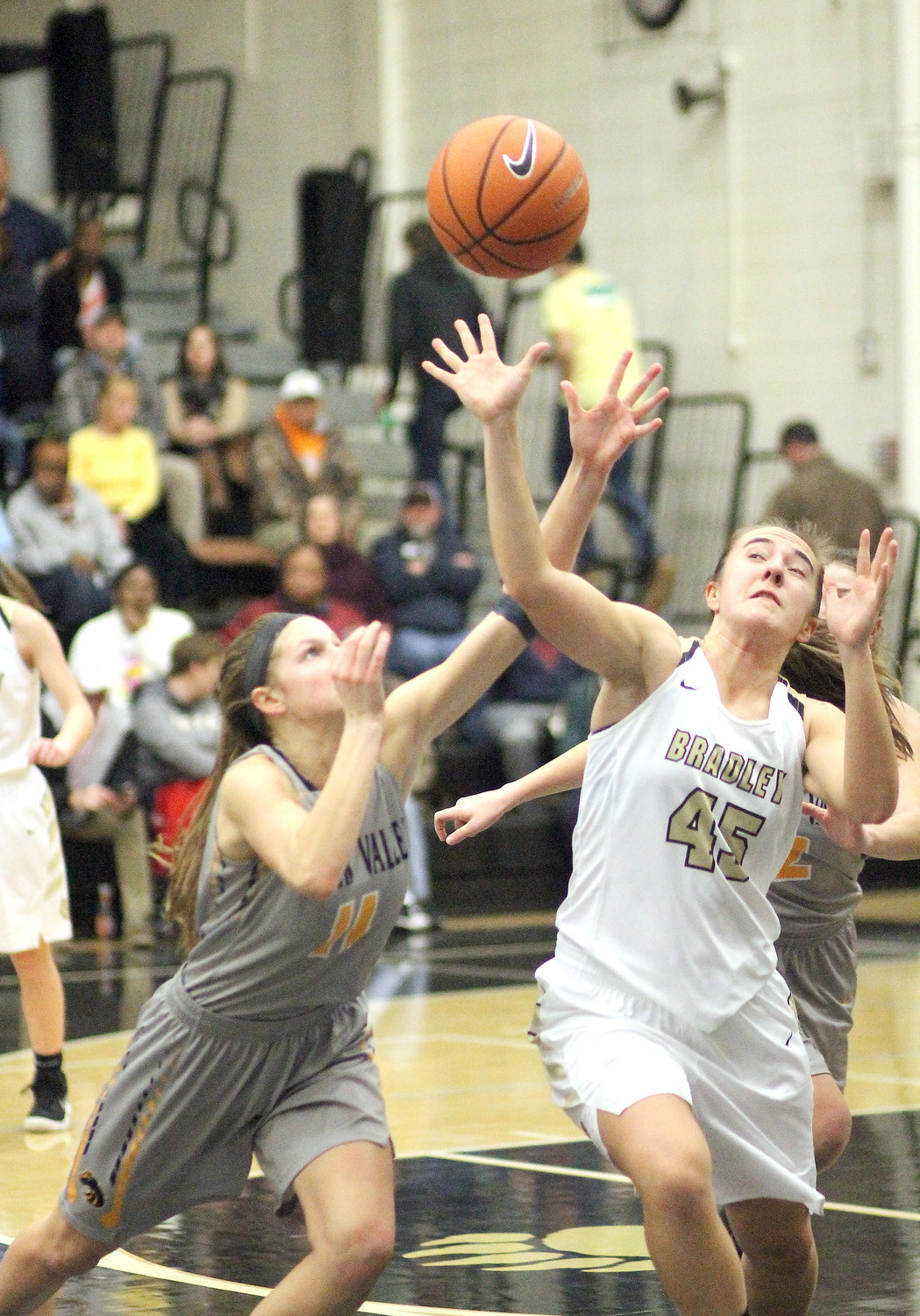 WALKER VALLEY senior Emily Anderson (11) and Bradley Central senior Hannah Lombard (45) battle for a loose ball during Friday evening's cross-county rivalry game at Jim Smiddy Arena.