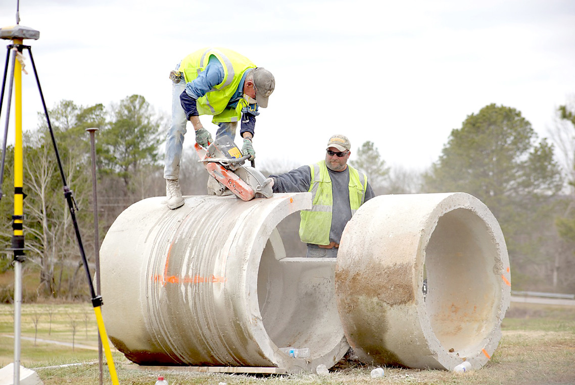 THE WORKMAN at right applies water to a tile-cutting project as a co-worker operates a saw. The huge tile are to be used in the water detention area of the new Legacy Village complex off Candies Lane.