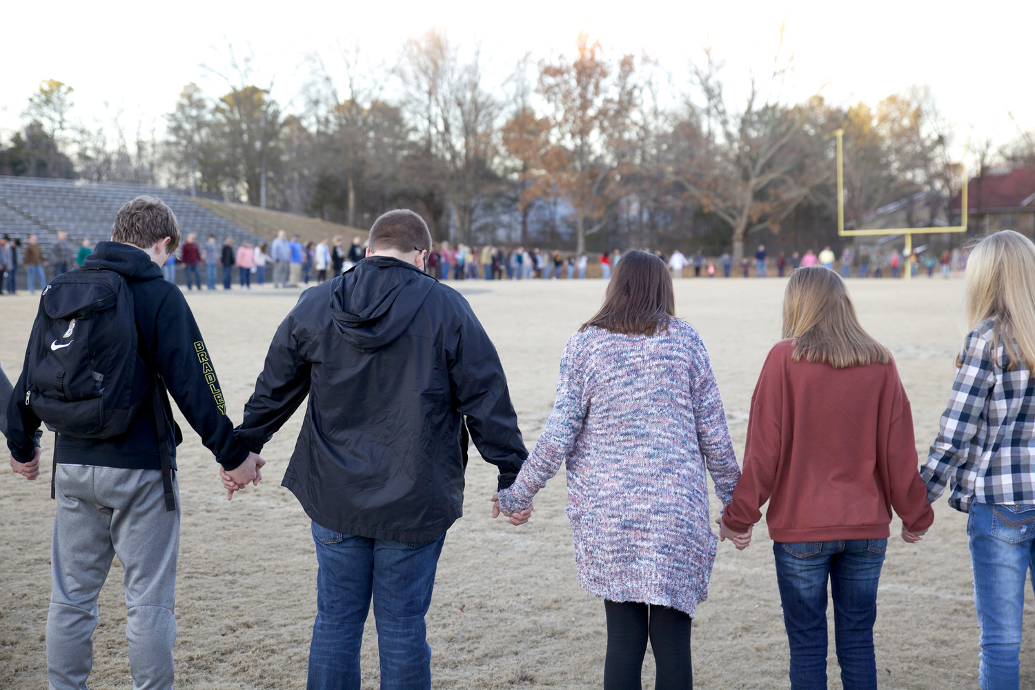 ATTENDEES HOLD HANDS and bow their heads within the circle of prayer on the BCHS football field during the Prayer Revival on Sunday, Jan. 21.
