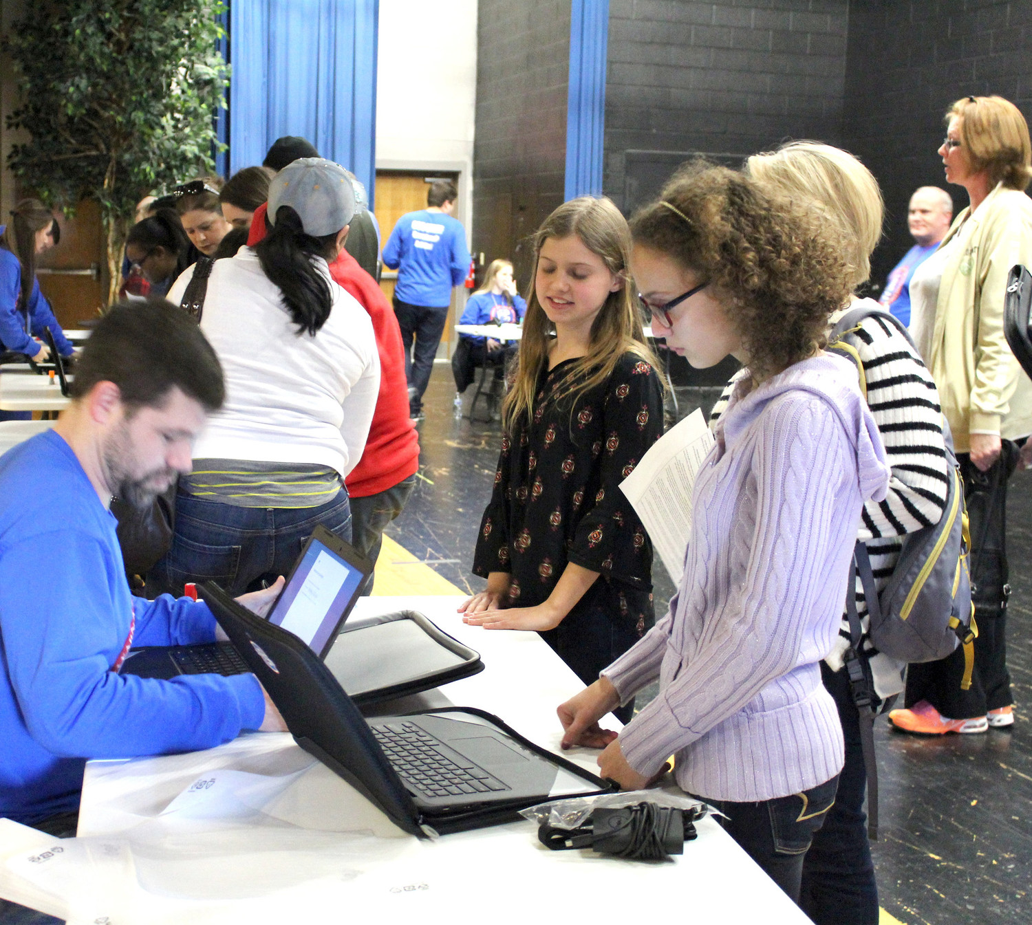 TUDENTS wait eagerly as a school staff member helps them sign into their new laptop computers at Cleveland Middle Schools. The school just issued laptop computers to each of its students.