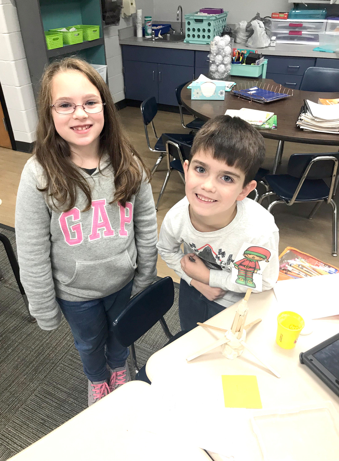 Ms. Koger and Mrs. Lee's first-grade classes at Taylor Elementary school have enjoyed experimenting with some awesome STEM activities. One involved seeing which team could build the tallest shelf for their elf (to keep it out of the reach of little hands). Since an elf looses its magic once it is touched, this was an important task. Students used Play-Doh and popsicle sticks to build their shelves. Each group had three chances to build the tallest without it falling. They used rulers to record heights and try to build the next shelf even taller. It was a great teamwork-building activity, and allowed for lots of creativity.