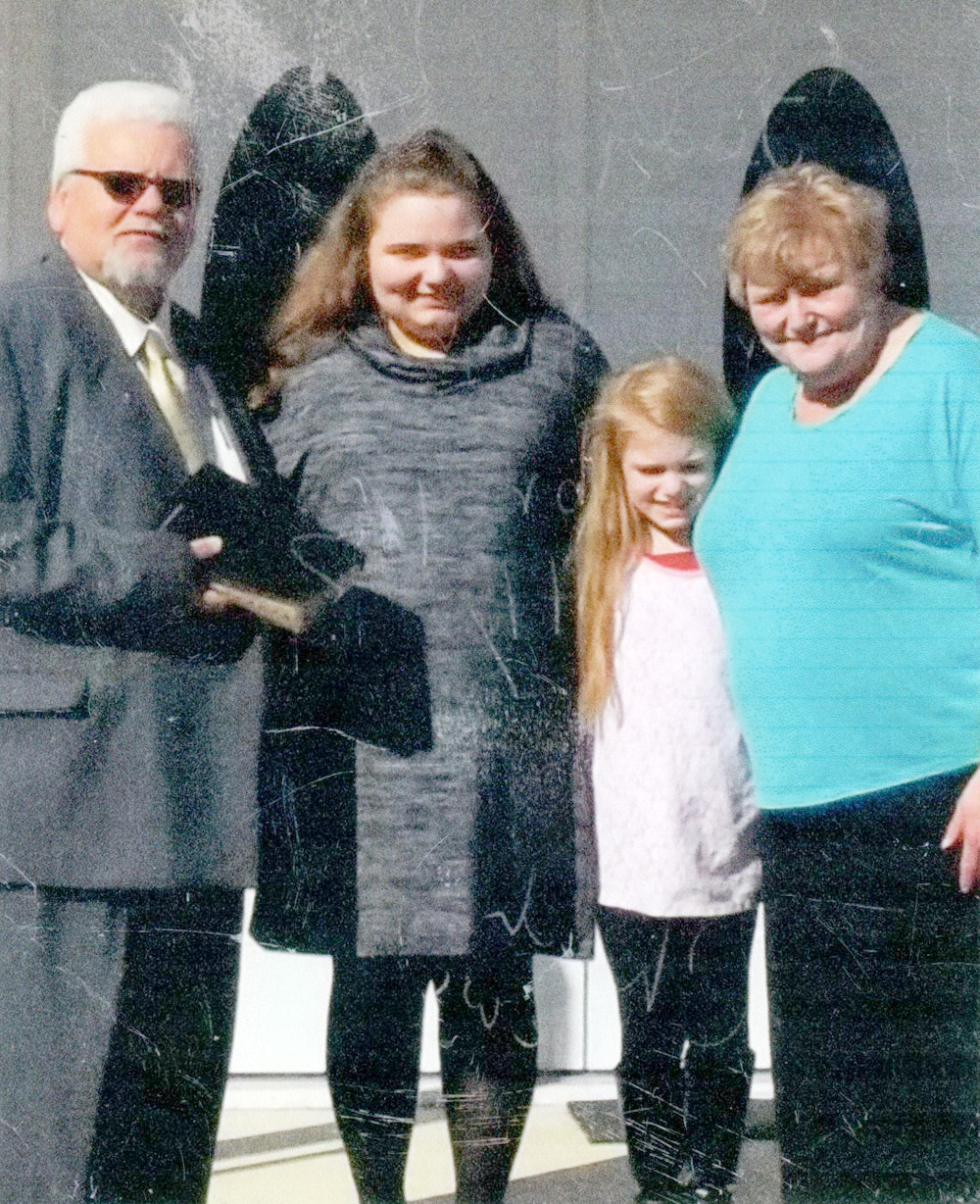 The Rev. Ronald L. Ledford, left, stands with his wife, Judy, right, and grandchildren Kaitlyn and Aubrey in front of Bethel Baptist Church.