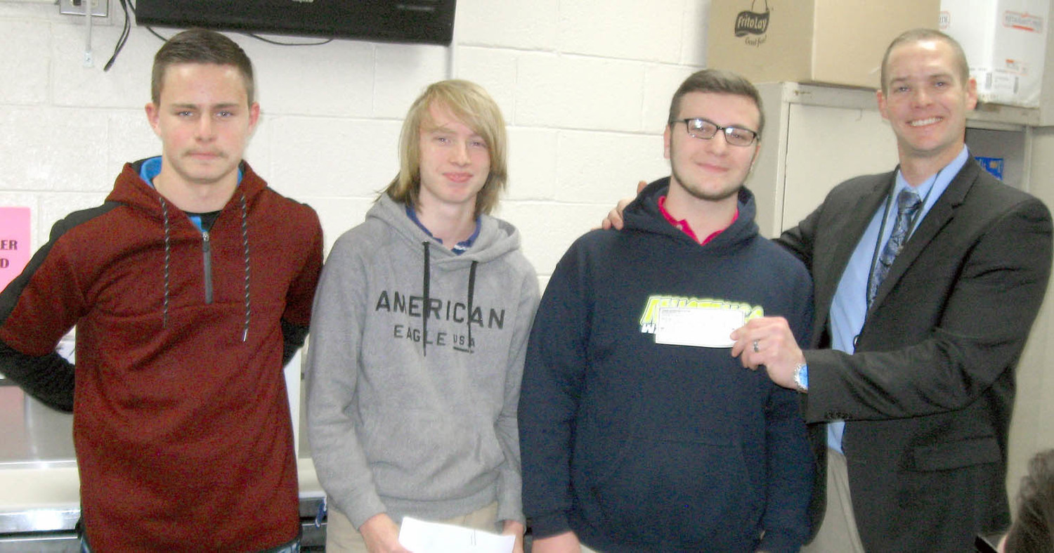 GOAL ACADEMY Principal Kyle Page, right, accepts a $610 donation from students Tyler Hicks, Mark Curry and Chris Folsom. The students donated the profits they made through Junior Achievement's Company program. 