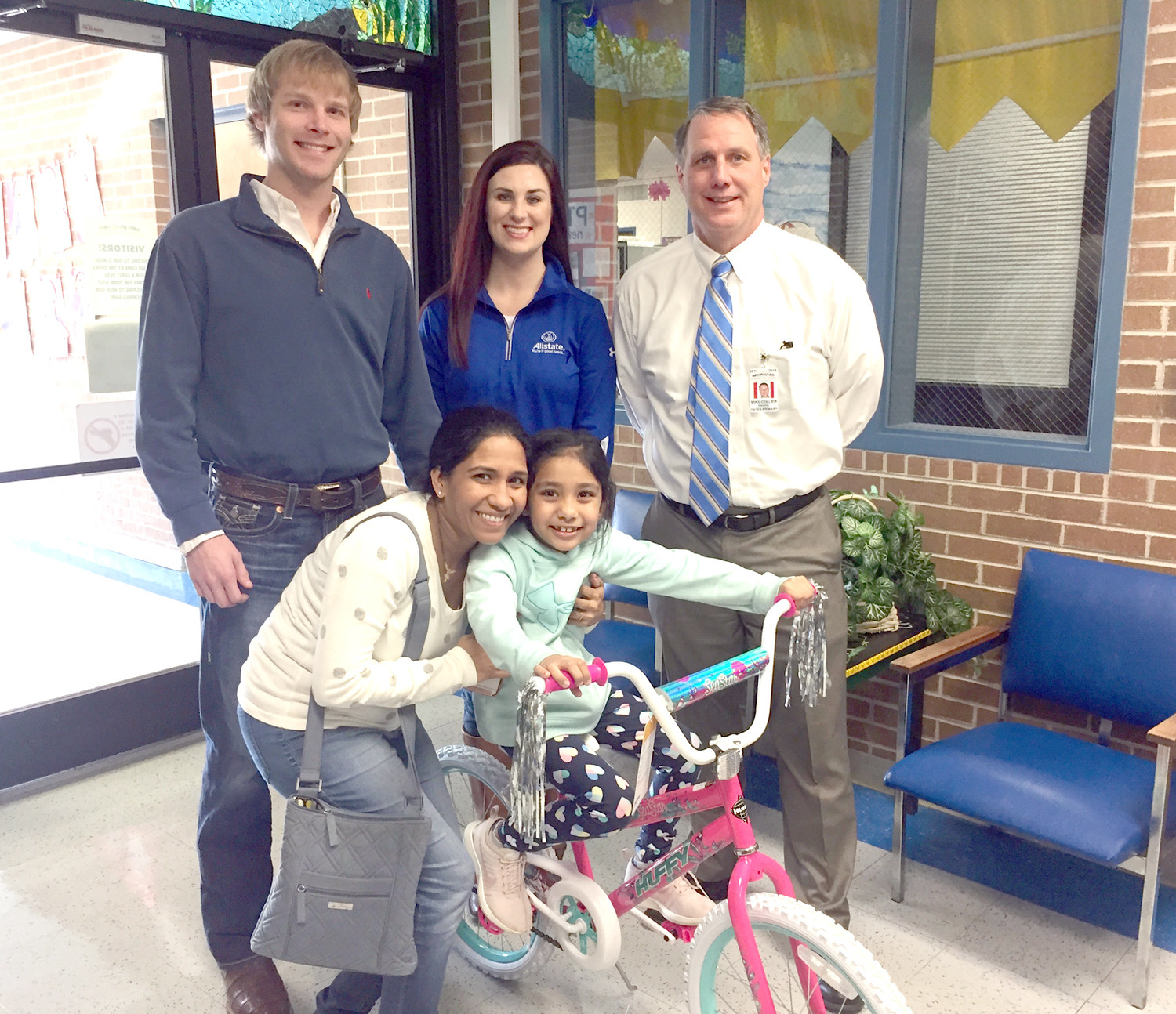 Grant Johnson's Allstate Agency presented a bicycle to Aarzoo Patel at Yates Primary School, for having perfect attendance for the past nine weeks of school. Standing from left are Grant Johnson, Randi Johnson and Yates Principal Mike Collier. Hina Patel celebrates with her daughter, Aarzoo, in front.