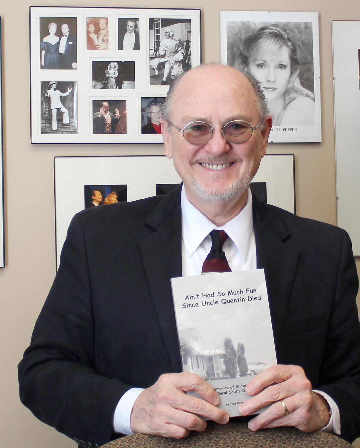 "TONY DEATON STANDS in his office at Lee University surrounded by photos from his professional opera career. Deaton is holding a copy of his memoir, ""Ain't Had So Much Fun Since Uncle Quentin Died: Memories of Growing Up in Rural South Carolina."""