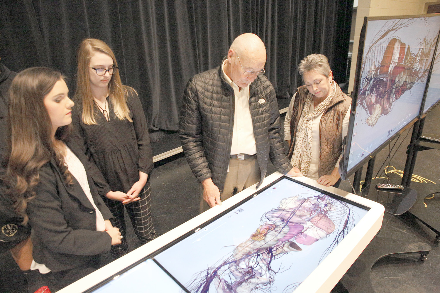 "STUDENTS AND PROFESSIONALS alike find value in the ""the world's first virtual dissection table,"" the Anatomage table on display at an open house event on Monday night at Bradley Central High School. Second from right, chief medical officer for Tennova, W.F. Johnson, tours the different systems of the body within the virtual cadaver.  This Anatomage table is one of two tables recently acquired by the Bradley County Schools system, the other being at Walker Valley High School.  From left are Olivia Dillard, Mattie Jones and Tammy Roberts."