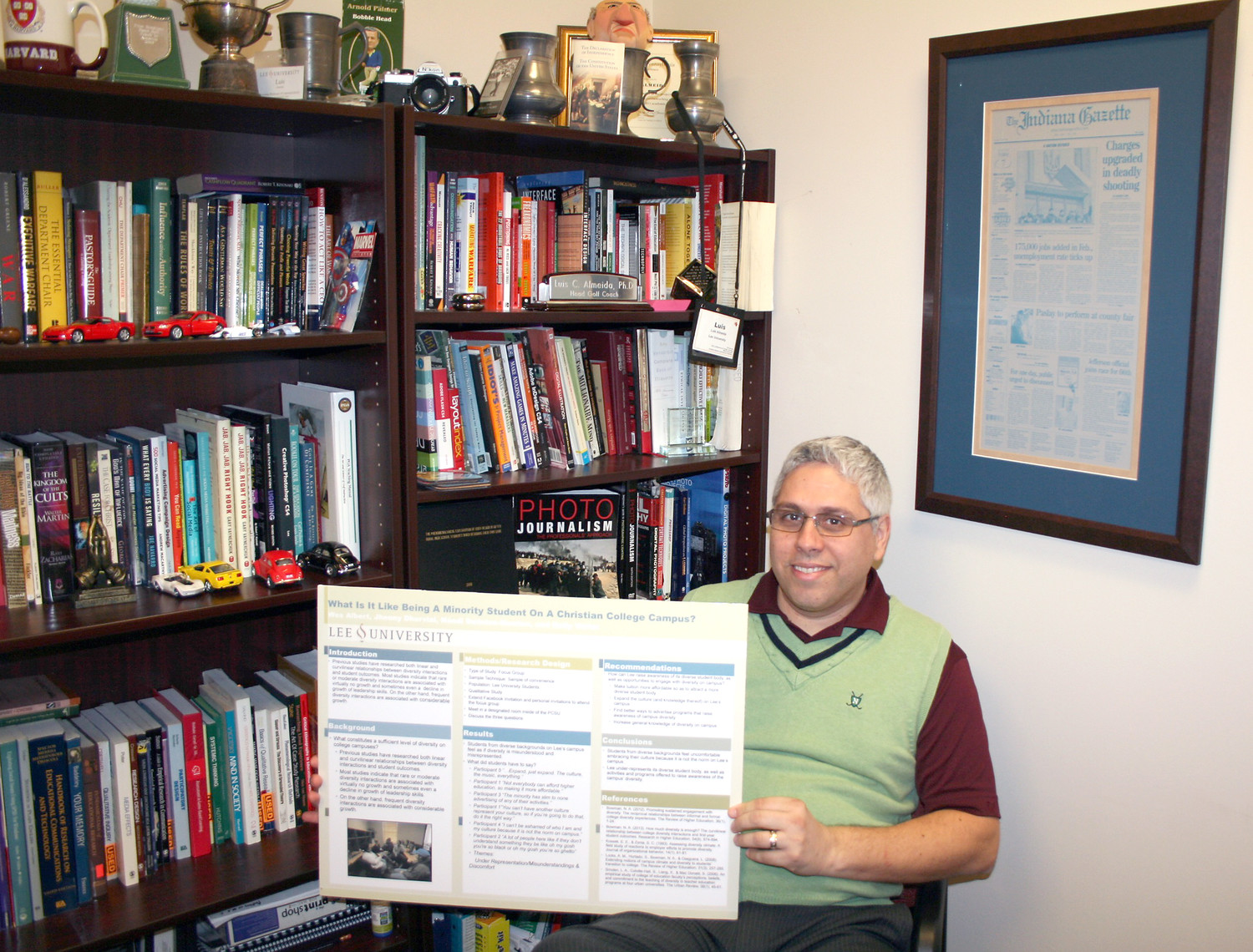 "SURROUNDED by his golf trophies and book collection, Dr. Luis Almeida displays a promotional poster that his students created titled, ""What's it like being a minority student on a Christian college campus?"" Almeida says work like this is much more immersive than simple exams."