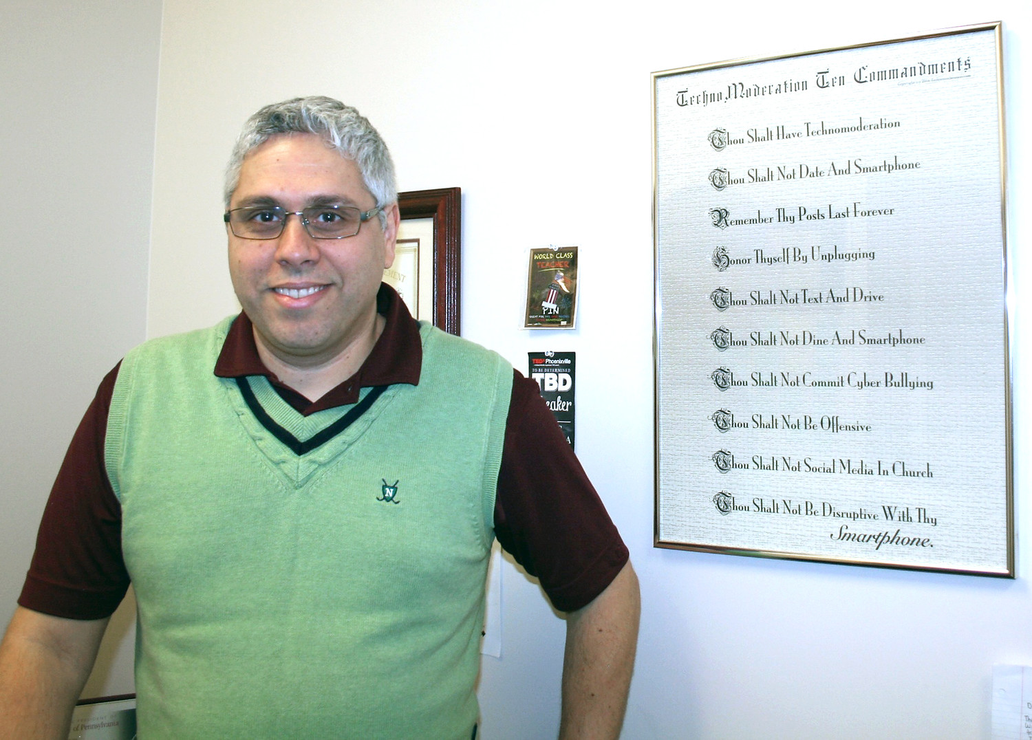 "DR. LUIS ALMEIDA stands with his framed ""TechnoModeration Ten Commandments"" poster in his office at Lee. Some of the commandments include, ""Thou Shalt Not Date and Smartphone,"" and ""Remember, Thy Posts Last Forever."""