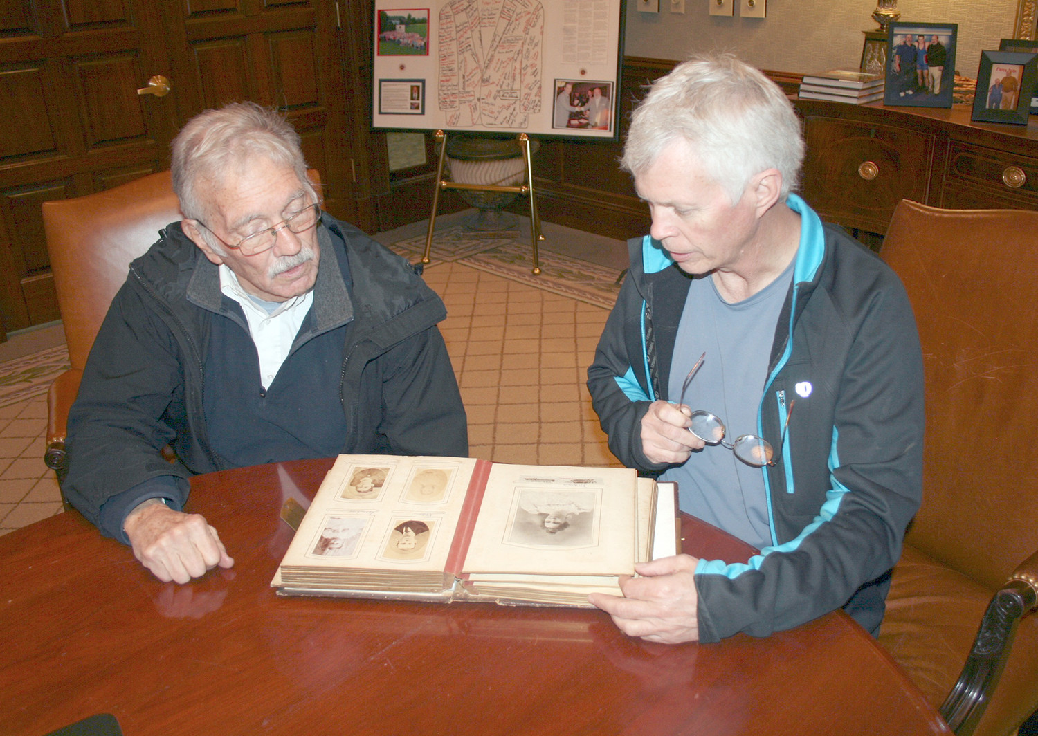 Charlie Corn, left, and Mitchell Guinn, right, look over one of the two newly discovered Hardwick family albums together.