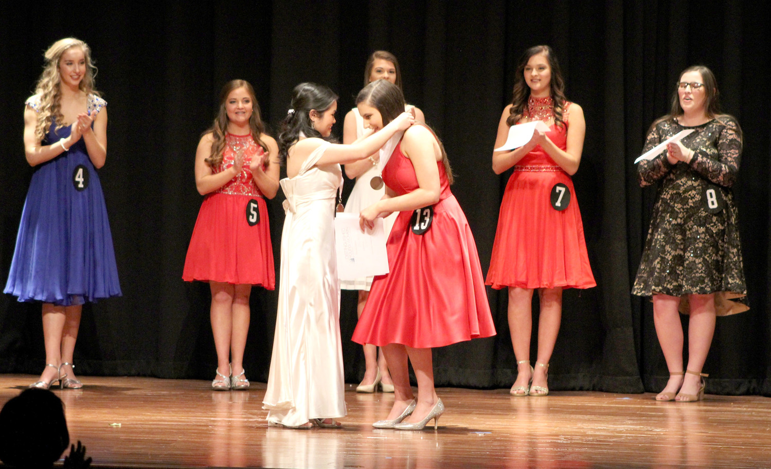 A SURPRISED Elena Burton prepares to receive her medallion from Jasmine Ngo, during Cleveland's recent Distinguished Young Women competition.