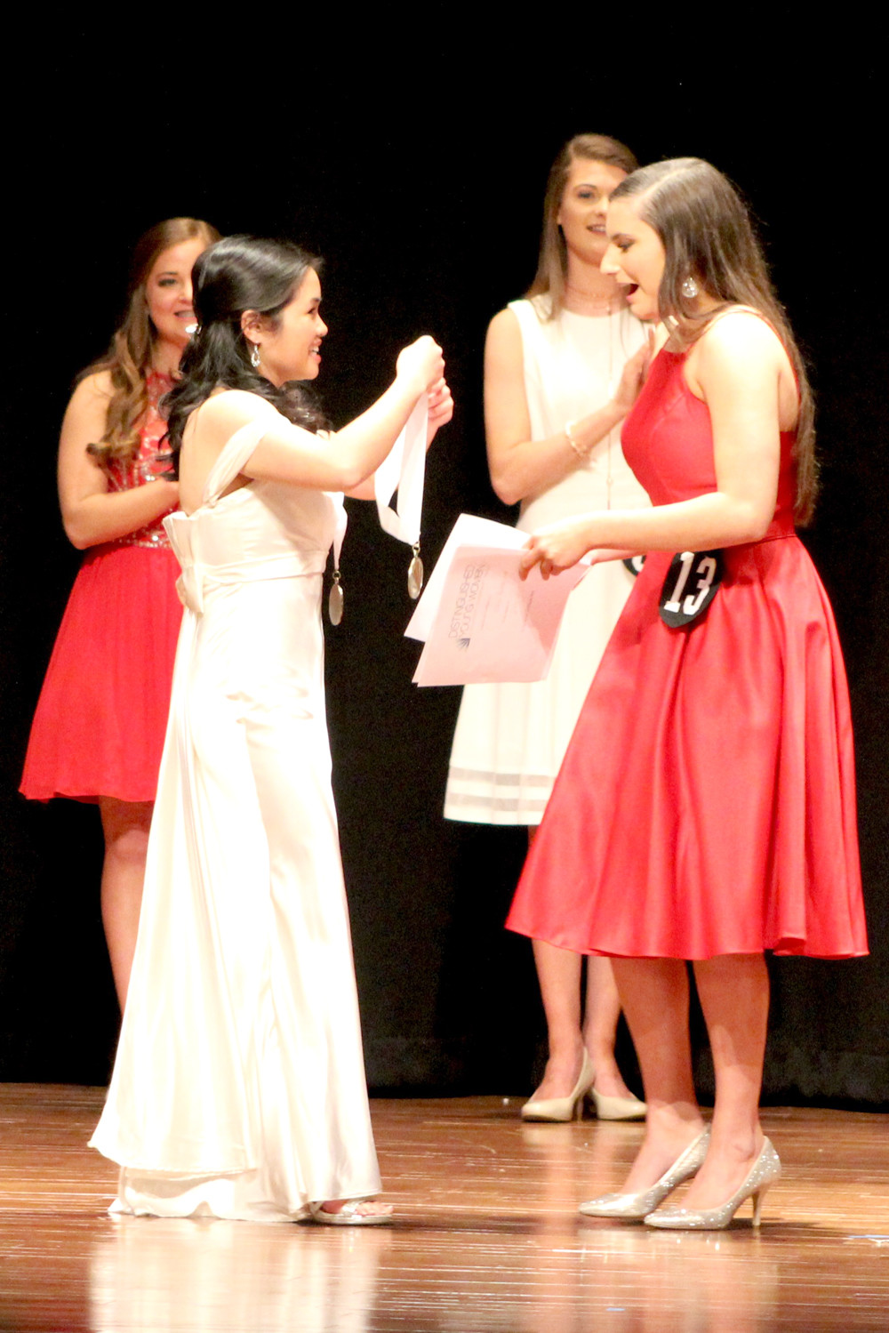 JASMINE NGO, Distinguished Young Woman of Cleveland for 2018, places a medallion around the neck of the 2019 title-holder, Elena Burton.
