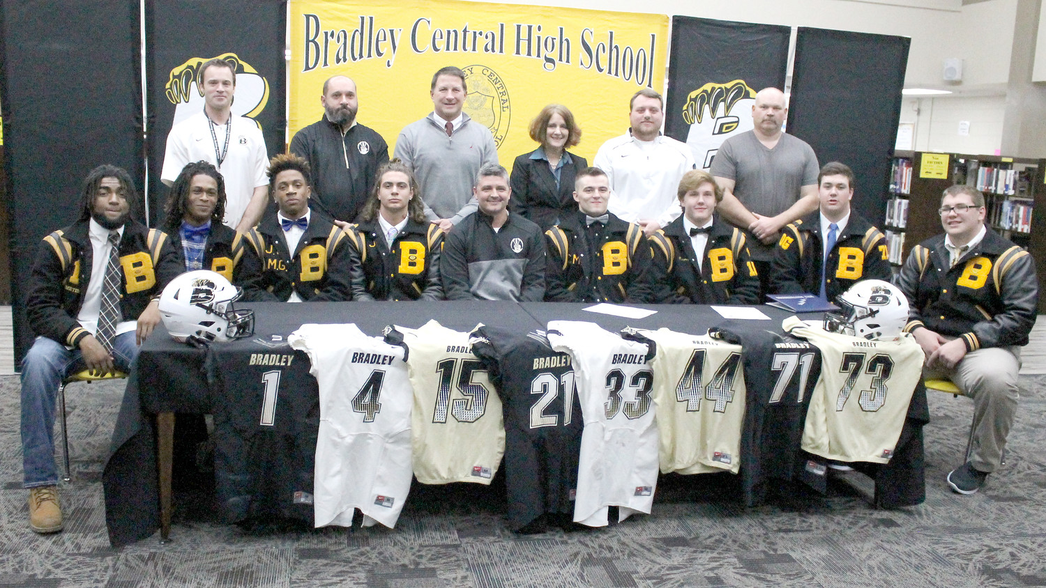 BRADLEY CENTRAL had a record eight football players officially announce their collegiate choices during Wednesday's National Signing Day ceremonies. Moving to the next level are, seated from left, Jay Person (Appalachian State), Jeffrey Brewer (Shorter), Lameric Tucker (UT-Chattanooga), Jordan McIllwain (Shorter), Bear head coach Damon Floyd, Kevin Gentry (Maryville), Adam Mullis (Maryville), Chris Cash (Air Force) and Tyler Collier (Thomas More). Helping them celebrate with family and friends were, standing from left, BCHS assistant coaches Isaac Robinson, David Phillips, BCHS Principal Todd Shoemaker, BCS Director of Schools Linda Cash, and Bear assistants Matt Moody and Blake Gideon.