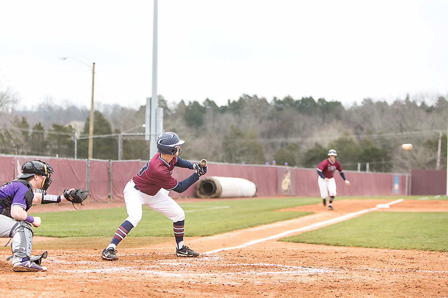 FLAMES junior Brayden Ware prepares to execute a squeeze bunt in Tuesday's game. The runner scored on the successful bunt.