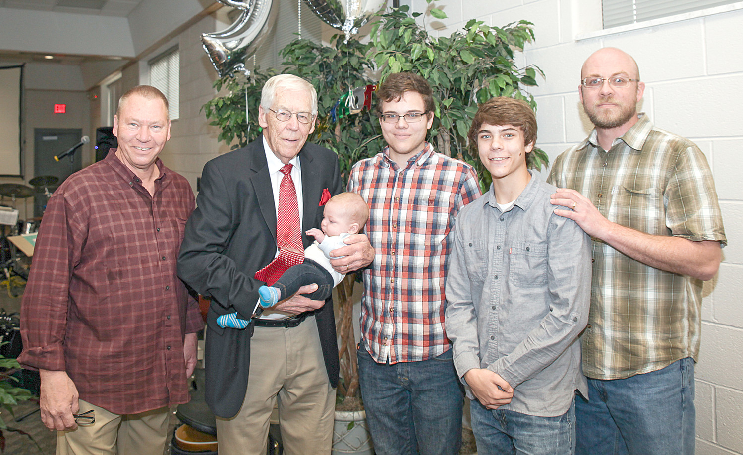 DR. WILLIAMS,center, stands in the midst of five generations of Williams. From left are Mike Williams, Dr. Williams holding Rhett Williams, Michael Williams, Alex Williams and Shaun Williams.  Dr. Williams has two children, Mike Williams and Marci Webb, not pictured; two grandchildren; five greatgrandchildren; and one great-great-grandchild.