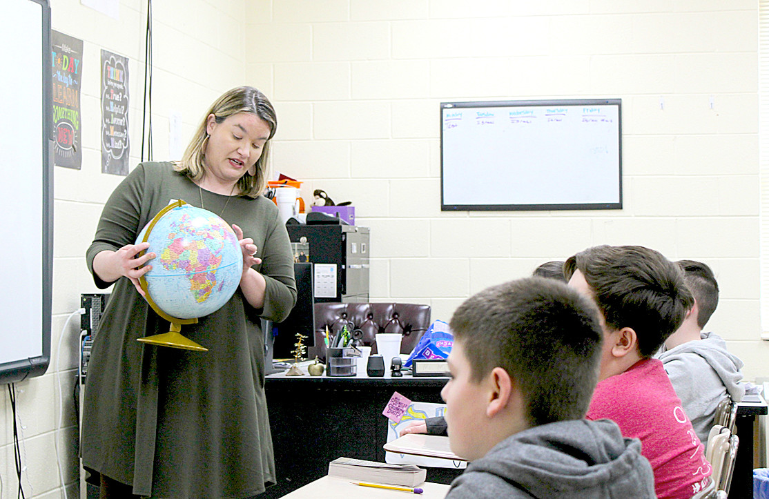 POINTING OUT Japan on a globe, Victoria White of Denso begins her presentation to sixth-grade students at Ocoee Middle School.