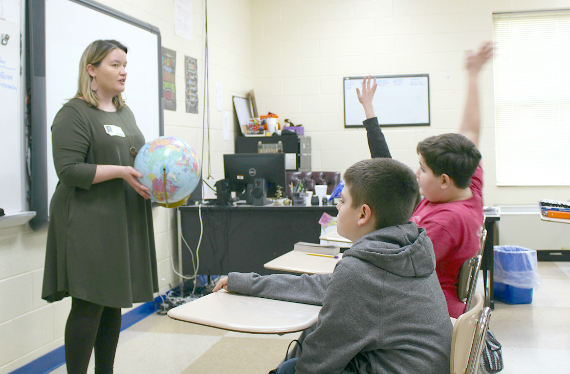 STUDENTS raise their hands as Victoria White of Denso invites questions about Japanese culture, during her visit to Ocoee Middle School.