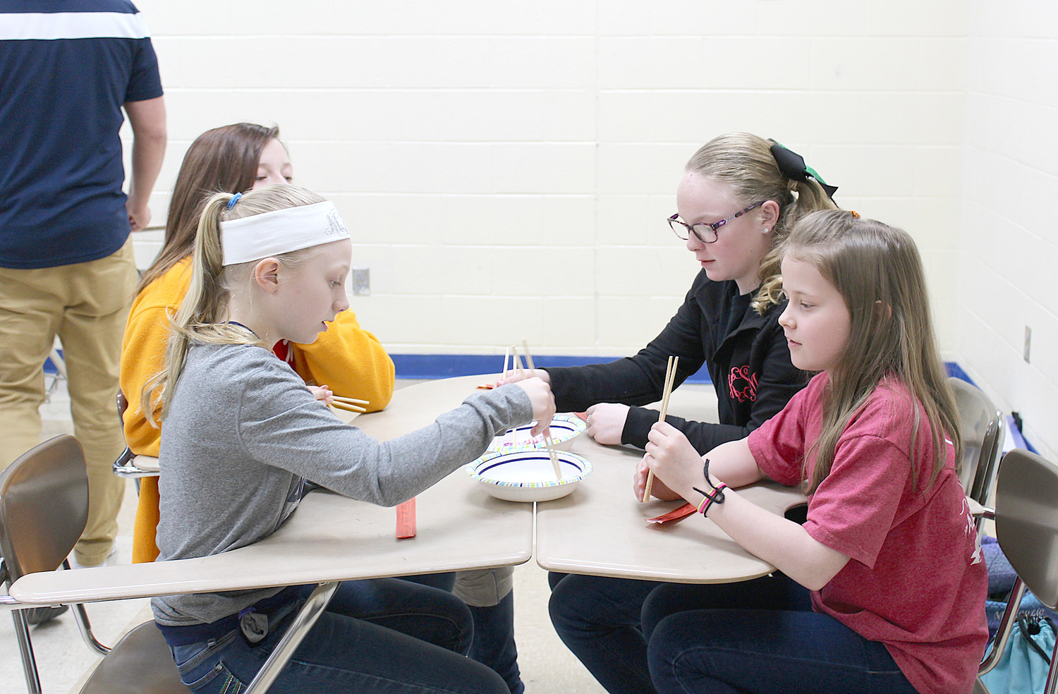 CONCENTRATING on the task at hand, Ocoee Middle School students play a game using chopsticks. Victoria White of Denso led students in this activity during her recent presentations on Japanese culture.