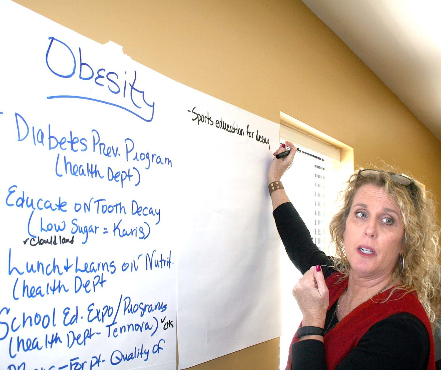 KAREN SLATER stands with an obesity posterboard as she writes down local programs intended to address this particular health issue. Other teams tackled different issues such as sexually transmitted infections, alcohol and substance abuse, smoking and physical inactivity.