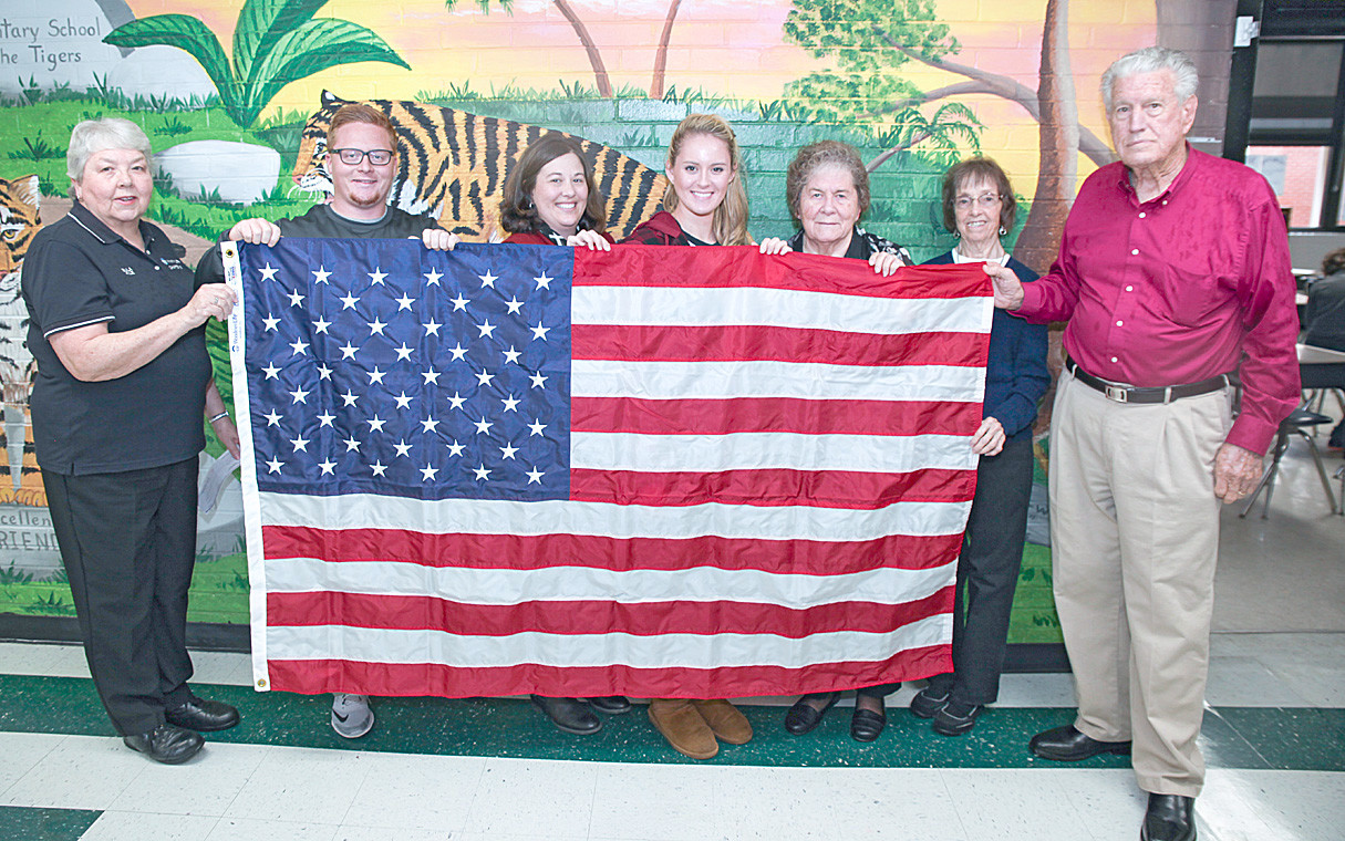 WOODMEN LIFE REPLACED the American flag for Taylor Elementary on Thursday, March 1. From left are Eula Kile, fifth-grade teacher, Nate Mathis, fourth-grade teacher, Alice Smith, fourth-grade teacher, Amanda Reagan, Joyce Johnson, Christine Miller and W.W. Johnson.