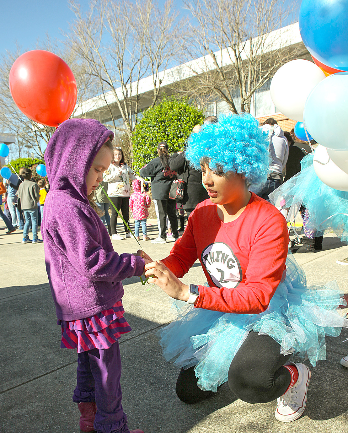 MAKINLEY WEISS, left, receives a red balloon from Isabel Tellez, dressed as Thing #2, while waiting in line to enter the CSCC Dr. Seuss Birthday Celebration inside the school library.