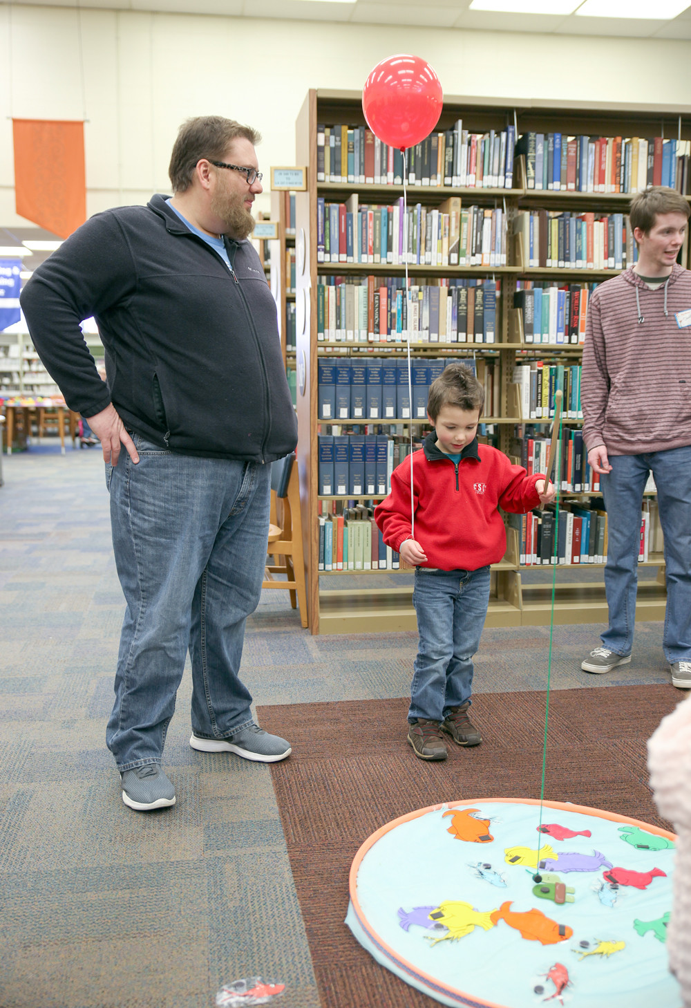CSCC BIOLOGY instructor, Jim Peters, left, watches as Holden Peters goes fishing during the Dr. Seuss event on Saturday.