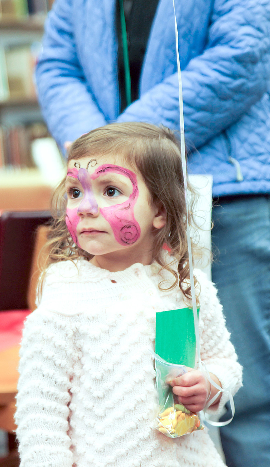 LITTLE AINSLEY PETERS, complete with her butterfly face paint, searches out her next next adventure at the Dr. Seuss celebration.