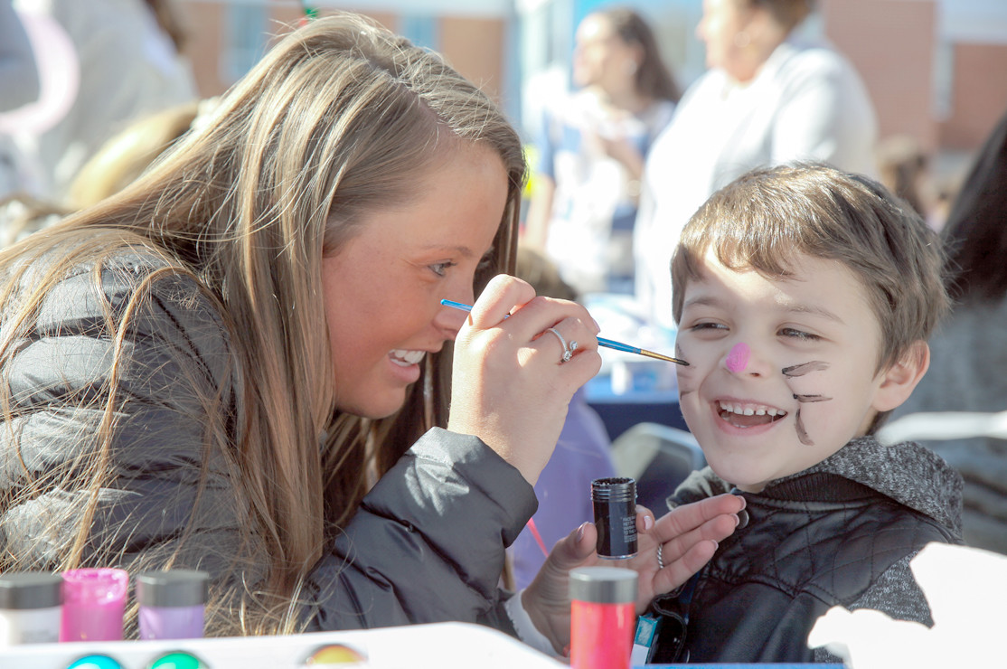 WINSTON BIBLE, right, smiles brightly while sitting for his face painting by Lauren Hines on Saturday.