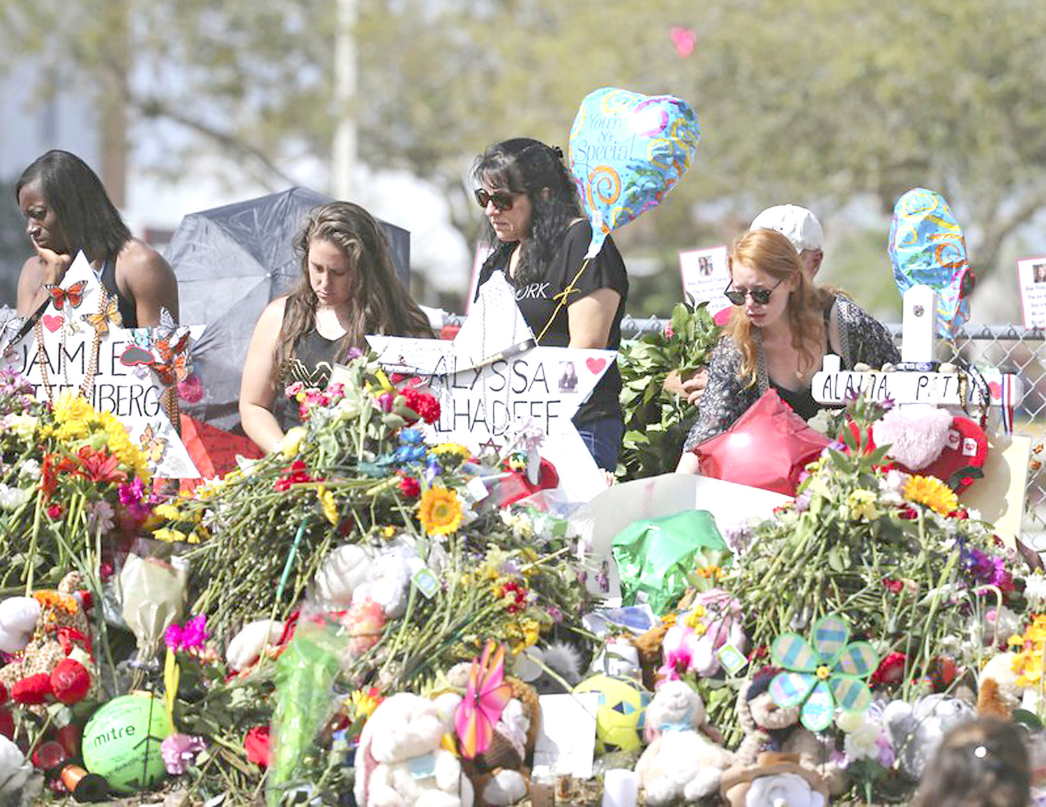 "MOURNERS BRING flowers as they pay tribute at a memorial for the victims of the shootings at Marjory Stoneman Douglas High School on Sunday, Feb. 25, in Parkland, Fla. A Bradley County native who serves as executive director of a professional teacher association in Tennessee is calling for government and elected leaders ""... to quit playing political football"" with school safety. Photo courtesy of David Santiago of the Miami Herald, via The Associated Press."