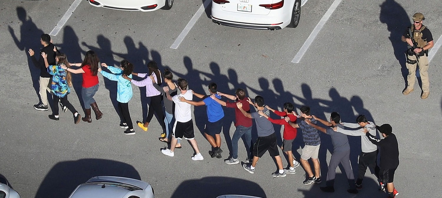 STUDENTS FORM a chain at Marjory Stoneman Douglas High School in Parkland, Fla., as they are brought out of the school following the Feb. 14 shootings. Photo courtesy of Joe Raedle/Getty Images.