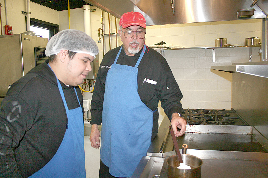Chef Rush works with student Paul Guillen on their large stovetop in his class' cooking battery.